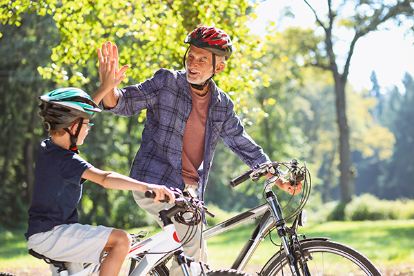 Grandfather and grandson high five for better bike riding