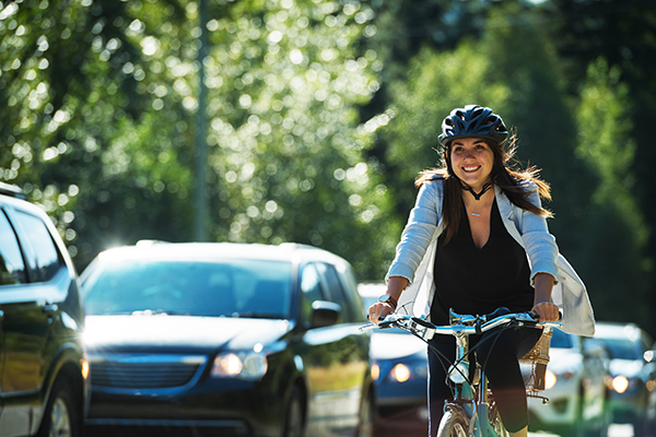 Female cyclist commuter  riding past traffic
