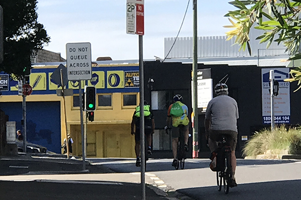 Bike riders coming up to traffic light in Rozelle