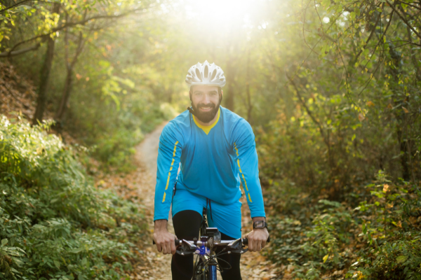 Male cycling in forest with smile on his face