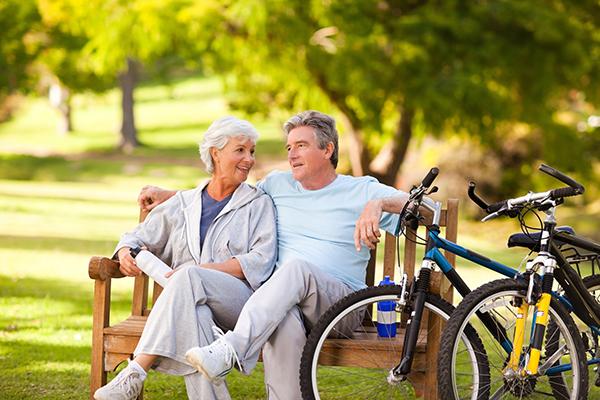 Senior Bike Riding Couple sitting on park bench smiling