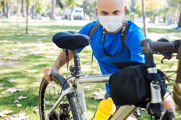 Bike riding wear mask while checking for mechanical fault in a park