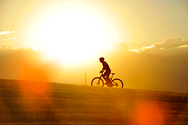 bike rider cycling up hill in the sunset