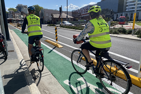 Cyclists in hi-viz safety vests riding in bike lane on Hunter St, Newcastle NSW