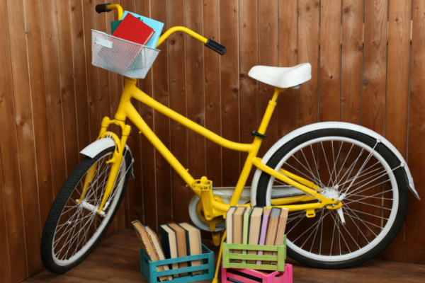 Books stacked in basket of yellow bike