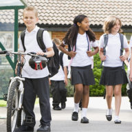 School boy walking his bike into school entry