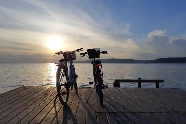 Two bikes stand on a wharf as sun rises