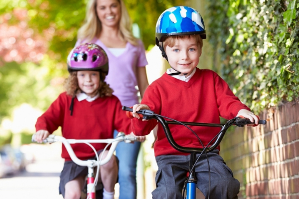 Young school children riding to school