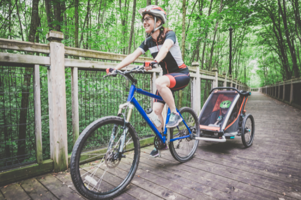 Millennial Parents Mother Biking with Toddler inside baby stroller