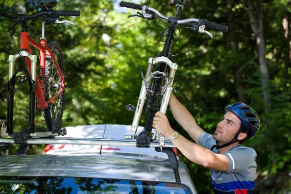 cyclist loading bicycle onto car roof racks