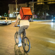 Food delivery bike rider on road at night