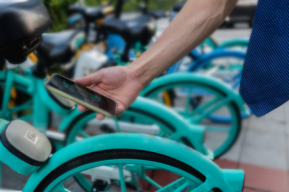 Business man unlocking share bike with mobile app