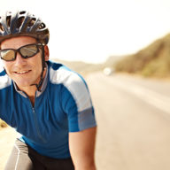 Smiling mature man on a bicycle with road and beach behind him